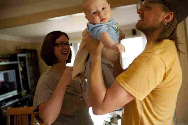 Dawn Heisey-Grove hands off Zane to Jonathan after a midday feeding. The couple were both working full time when Jonathan lost his job as a graphic designer two years ago.