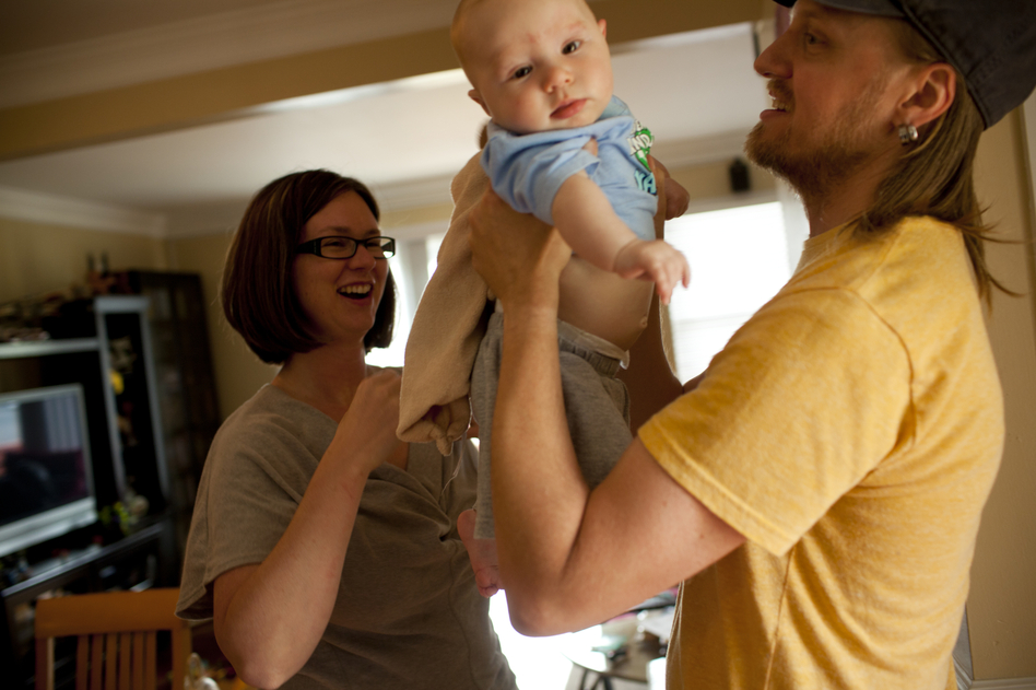 Dawn Heisey-Grove hands off Zane to Jonathan after a midday feeding. The couple were both working full time when Jonathan lost his job as a graphic designer two years ago. (Kainaz Amaria/NPR)