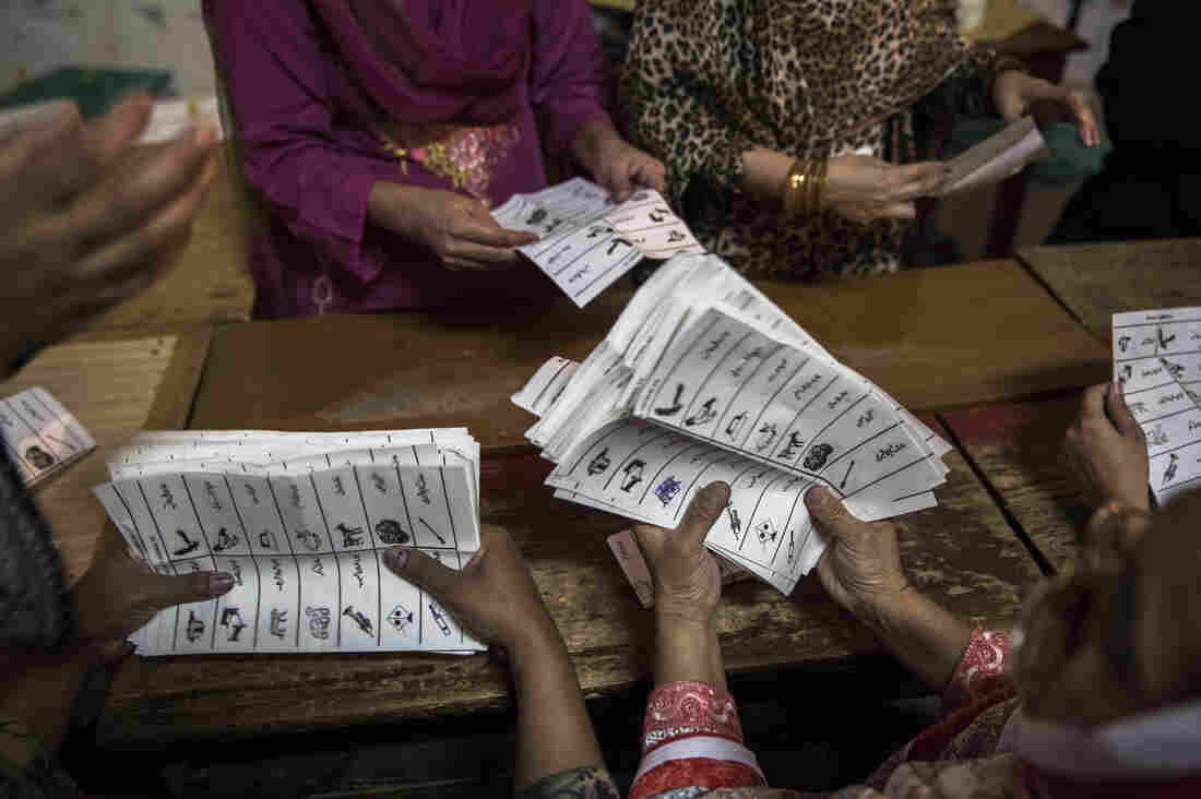 Election workers count ballots at a polling stat