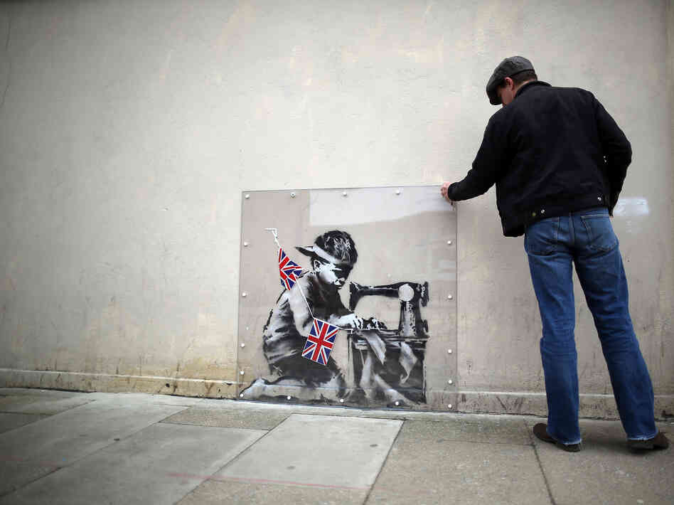 A man inspects a plastic cover placed over Slave Labour, an artwork attributed to Banksy, in London. This piece of art was