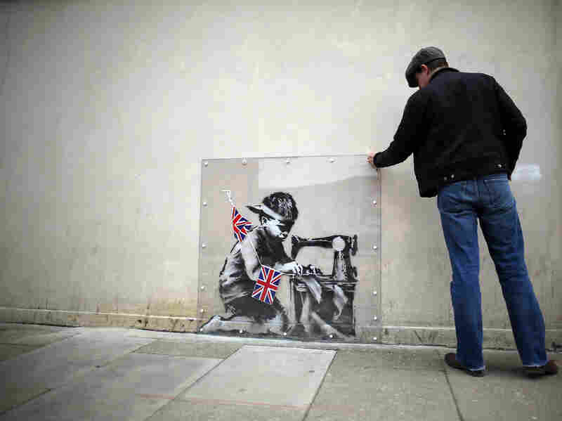 A man inspects a plastic cover placed over Slave Labour, an artwork attributed to Banksy, in London. This piece of art was put up for sale in Miami last February, but the ensuing outrage led to the auction's cancellation. The mural is now part of an exhibition in London, and is is expected to move to the U.S. afterward.