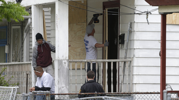 Workers board up the house where three women were held in Cleveland Saturday. Suspect Ariel Castro, who allegedly held three women captive for nearly a decade, is charged with rape and kidnapping. Sunday, the women asked for privacy and time to connect with their families. (AP)