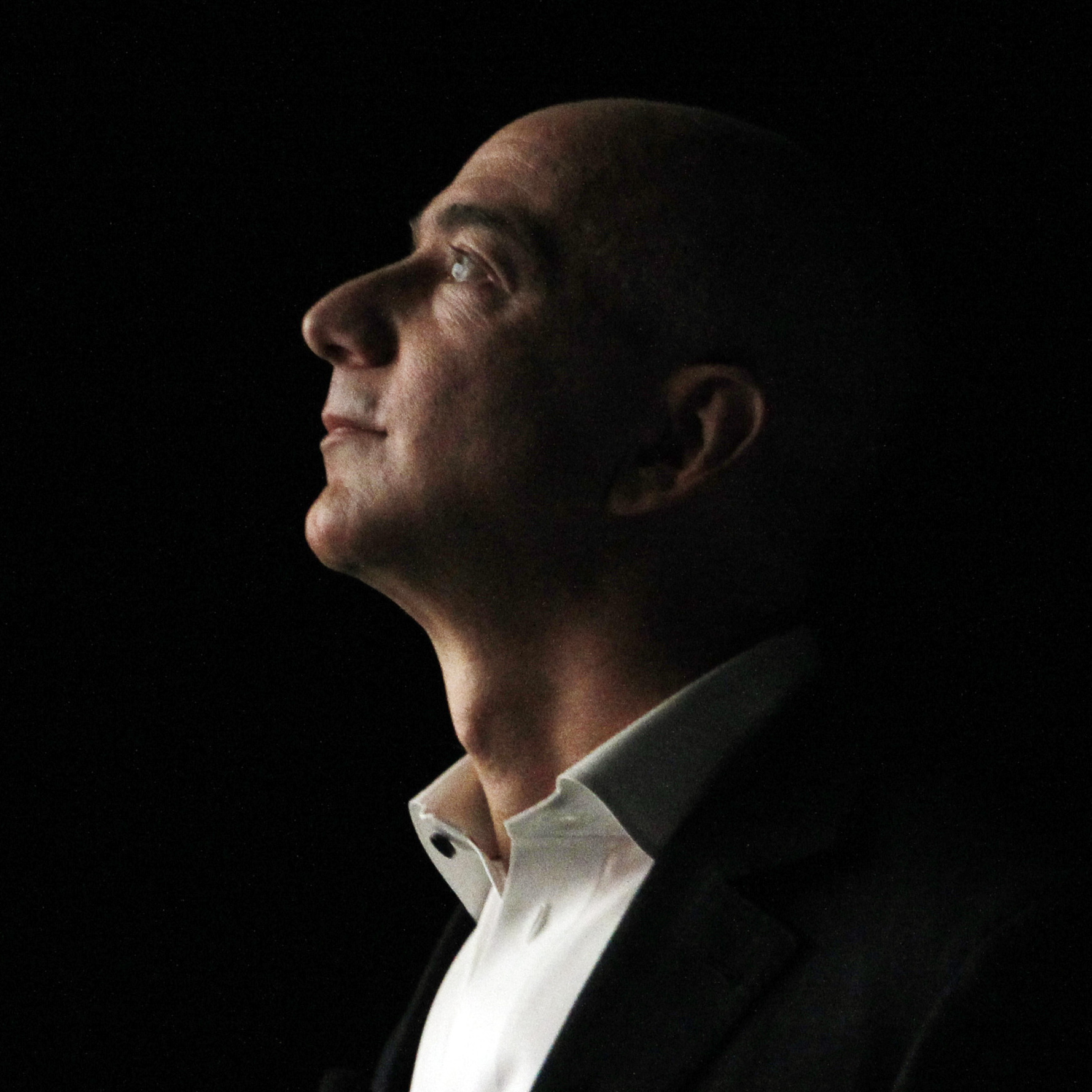 Jeff Bezos, CEO and founder of Amazon, is illuminated by a display screen at the introduction of the new Amazon Kindle Fire HD and Kindle Paperwhite.