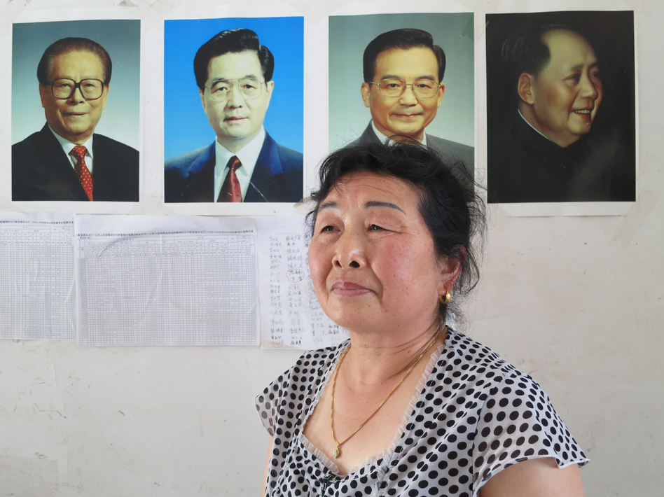 The wife of Li Yiqian, Yang Liming, sits in their house, which is plastered with pictures of China's leaders, an attempt to help prevent local authorities from demolishing it. Her husband has been sentenced to three years in prison for organizing a crowd to create a disturbance; she believes it's for his work in helping dispossessed villagers petition.