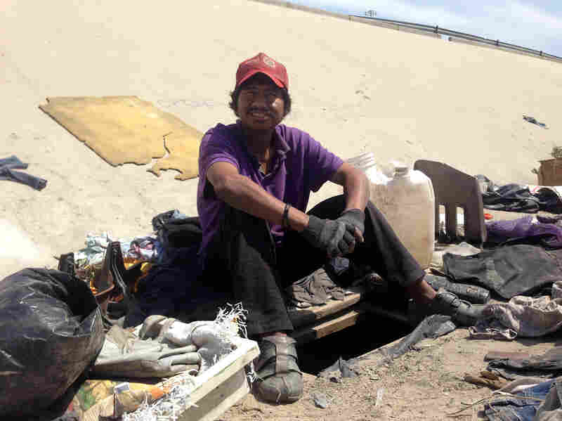 Abimael Martinez, who was deported from Riverside, Calif., sits next to the hole he dug to live in beneath the banks of Tijuana's fetid river canal.