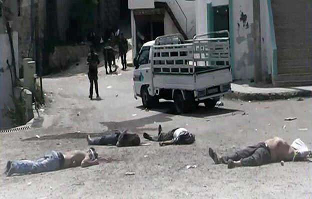 This image provided by the Syrian Revolution against Bashar Assad and released May 2 shows soldiers loyal to Syrian President Bashar Assad standing amid dead bodies at Bayda village, in the mountains outside the coastal city of Banias, Syria.