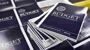 Copies of President Obama's budget plan for fiscal 2014 are prepared for delivery at the U.S. Government Printing Office in Washington in April. The Congressional Budget Office has sharply cut the outlook for the federal  deficit.