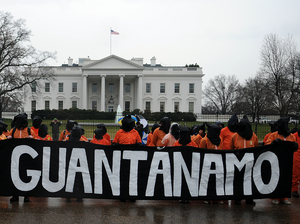 Protesters wear prison-style orange jumpsuits, handcuffs and hoods during a 2012 demonstration urging the government to close down the U.S. detention facility at Guantanamo Bay.