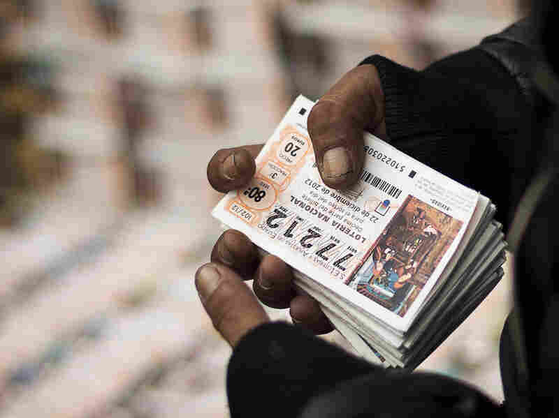 A seller holds a pack of tickets for Spain's 2012 Christmas lottery.