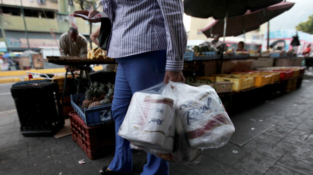 A woman who just bought toilet paper at a grocery store reads her receipt as she leaves the store in Caracas, Venezuela, on Wednesday. The government says it