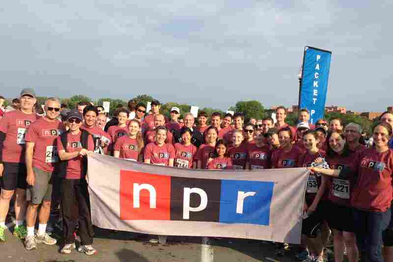 The full group, including NPR President and CEO Gary E. Knell (center, in the black sweatshirt), pose together behind the NPR banner after a successful finish.