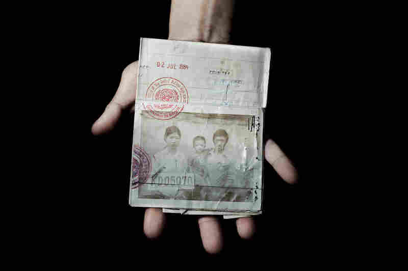 """Sonny Vaahn, 25, holds his family's refugee identification in the Bronx, N.Y. The card was issued to them during their initial entry into a refugee camp along the Thai-Cambodian border after the """"killing fields"""" atrocities ended in Cambodia."""