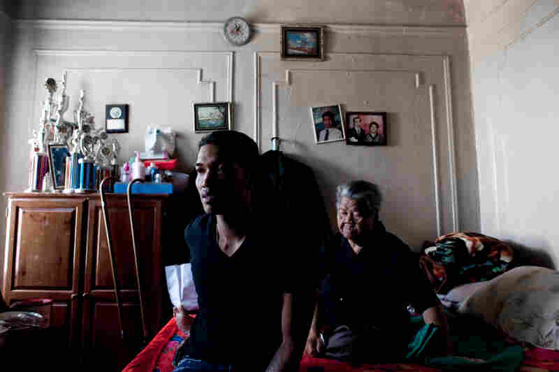 Sovann Ith, 23, sits alongside his grandmother, Somaly Ith, 83, in their living room in the Bronx, N.Y. The apartment complex was once predominantly Cambodian but is now home to five families.