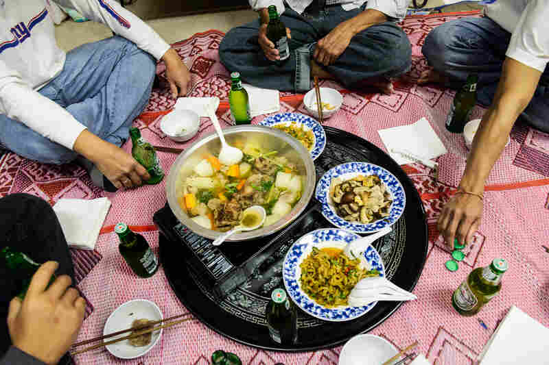 A traditional meal, on the ground with a floormat, in a Cambodian home in Philadelphia.