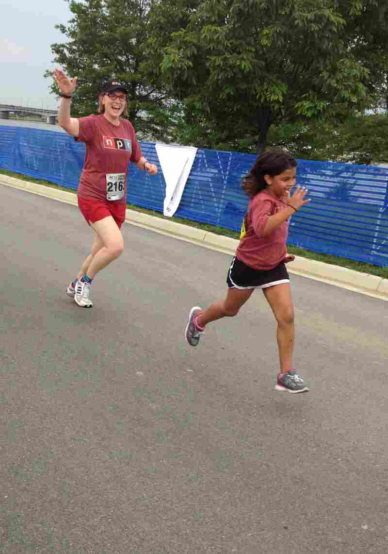 Waving to sideline supporters, All Things Considered Associate Producer and race Team Captain Justine Kenin is pictured here nearing the finish line with her daughter, Annie.