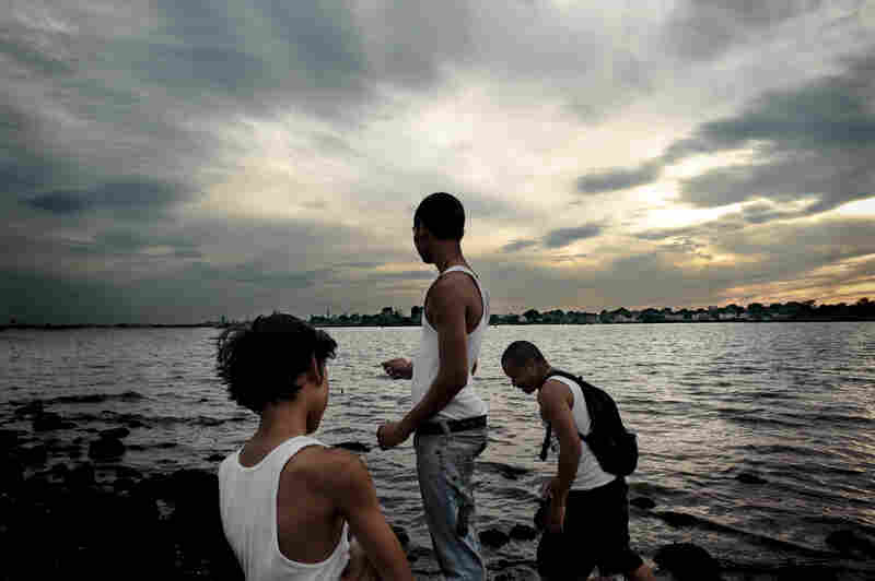 Joshua Vatthanavong (from left), 11, Joey Vatthanavong, 16, and Sanet Kek, 28, fish without poles at Ferry Point Park in the Bronx, N.Y.