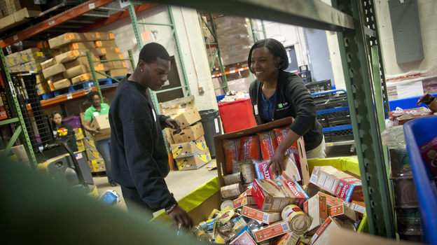 TD Bank volunteers sort donated food into barrels at the Manna Food Center in Gaithersburg in Montgomery County, Md. Poverty in the county just outside Washington, D.C., has grown by two-thirds since 2007. (NPR)