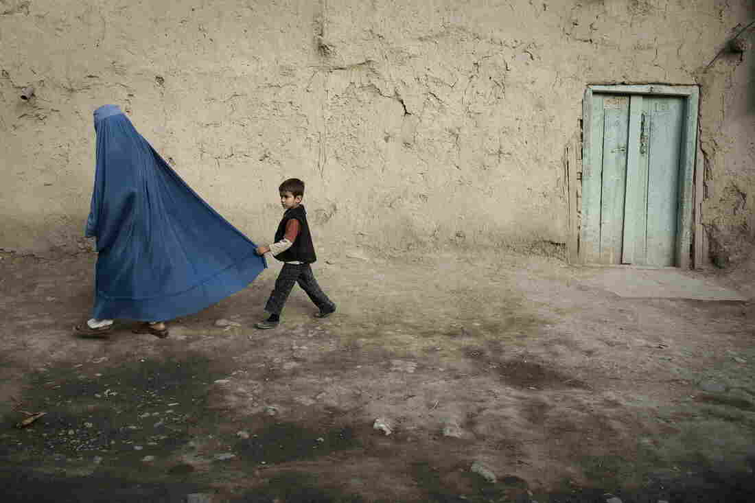 A boy holds the burqa of his mother as they walk down a street in the old city of Kabul on November 1, 2009.