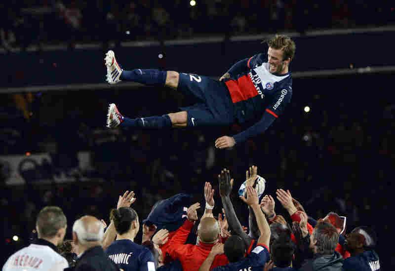 Paris Saint-Germain's English midfielder David Beckham is thrown in the air by teammates.