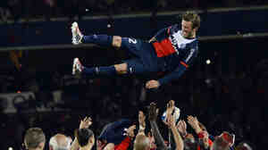 Paris Saint-Germain's English midfielder David Beckham is thrown in the air by teammates after a French L1 football match between Paris St Germain and Brest on Saturday at Parc des Princes stadium in Paris.