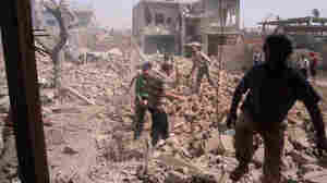 Syrians inspect Saturday the rubble of buildings damaged by government airstrikes in Qusair, Syria. The image was provide