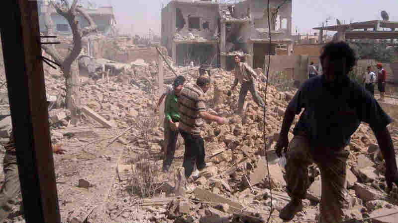 Syrians inspect Saturday the rubble of buildings damaged by government airstrikes in Qusair, Syria. The image was provided by Qusair Lens, and was authenticated based on its contents and other AP reporting.