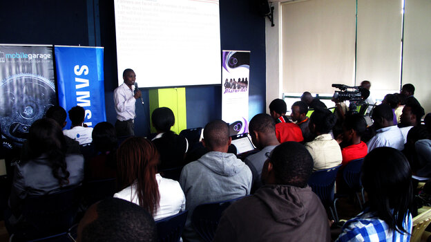 """Kenyans watch a presentation at the """"mobile apps garage showcase"""" this in Nairobi."""