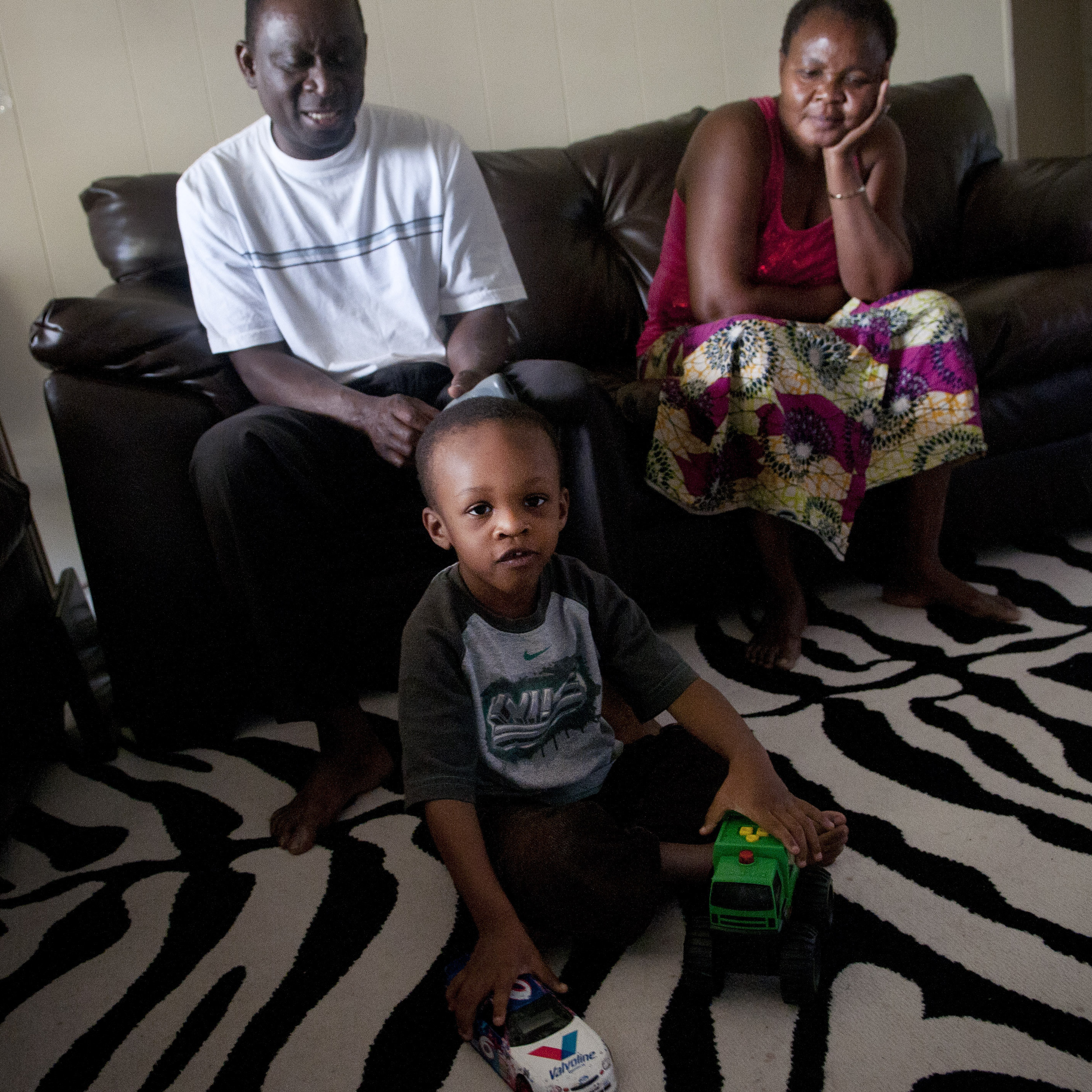 Fafaneva Phillip Avudufu (left) and his wife, Akouavi Davi, with their grandson Joshua, 4, in their apartment in Gaithersburg, Md.