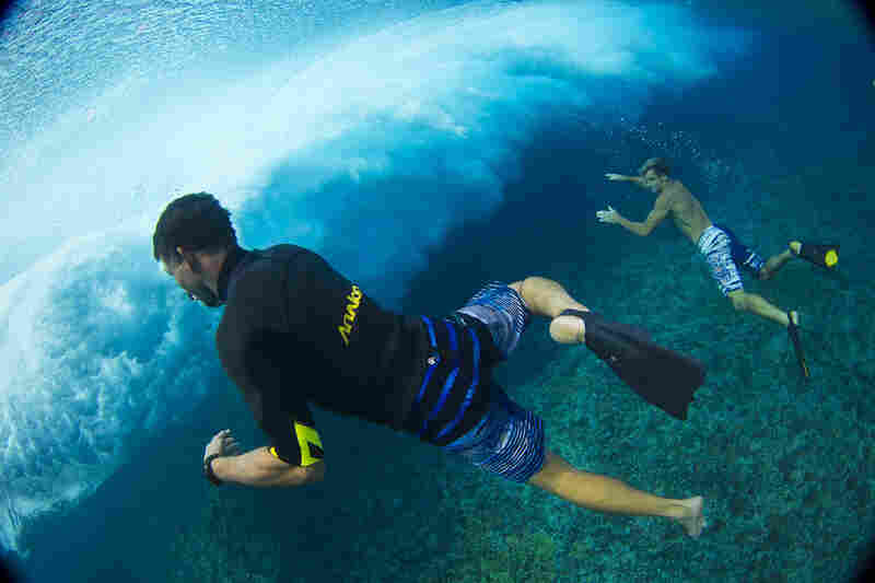 Kamalei Alexander and Laird Hamilton play in the Teahupoo waves.