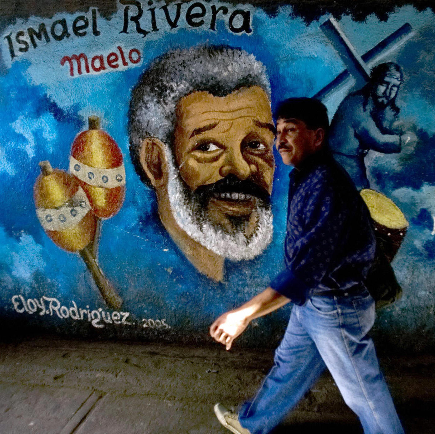 A man walks past a mural of Puerto Rican singer Ismael Rivera in the La Bombilla neighborhood of Petare, eastern Caracas, Venezuela.