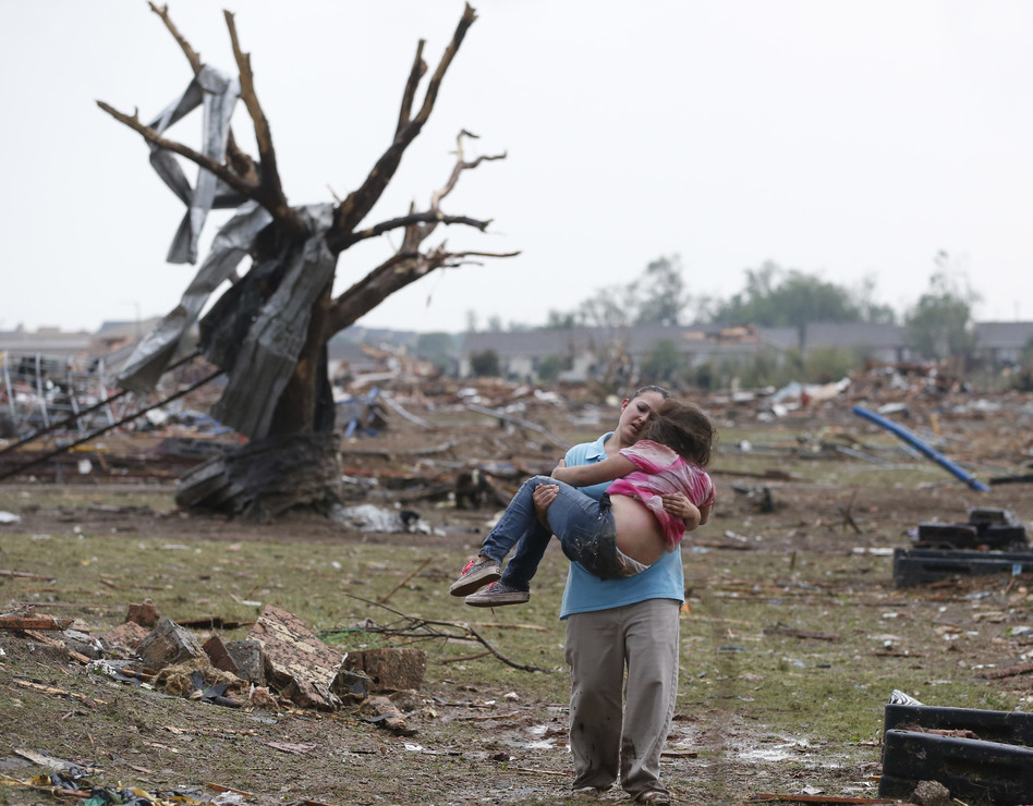 A woman carries her child through a field near the collapsed Plaza Towers Elementary School in Moore, Okla., on Monday A tornado as much as a mile wide with winds up to 200 mph roared through the Oklahoma City suburbs flattening entire neighborhoods, setting buildings on fire and landing a direct blow on an elementary school. (Sue Ogrocki/AP)