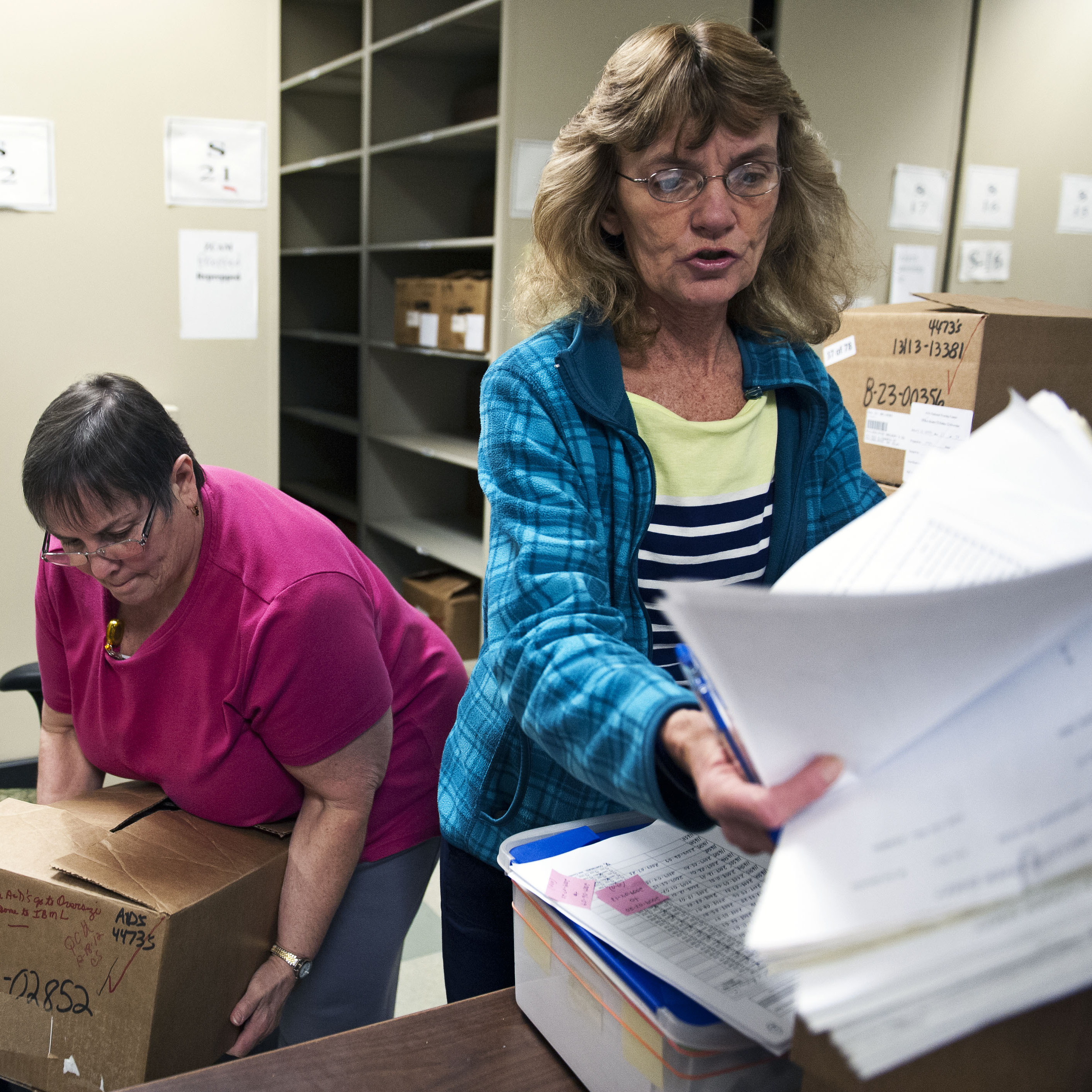 Document prep technician Carol Sine (left) and tracer Debra Barrett process firearm transaction documents at the National Trace Center in Martinsburg, W.Va.