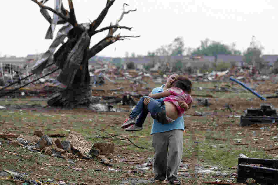 A woman carries her child through a field near the collapsed Plaza Towers Elementary School. The tornado flattened entire neighborhoods and set buildings on fire.