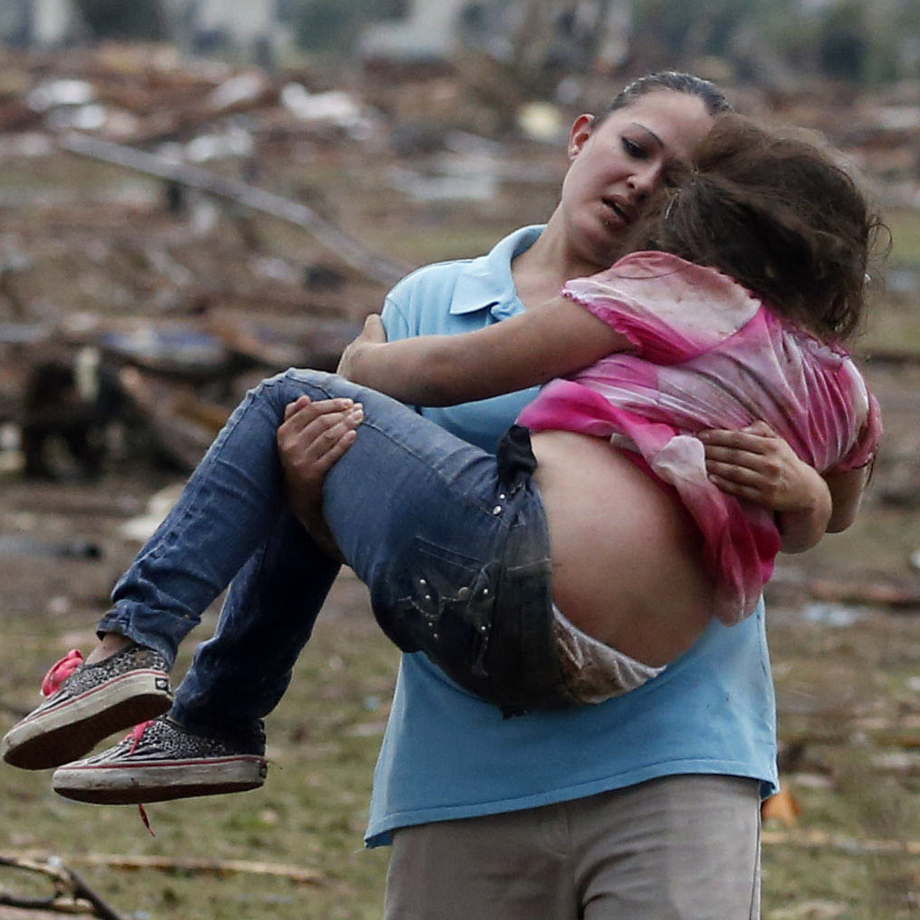 A woman carries her child through a field near the collapsed Plaza Towers Elementary School in Moore, Okla., on Monday. A tornado as much as a mile wide with winds up to 200 mph roared through the Oklahoma City suburbs.