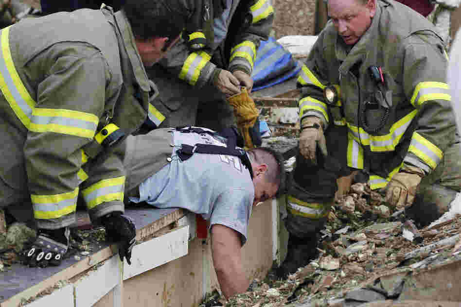 Rescue workers dig through the rubble of a collapsed wall to free trapped students at Plaza Tower Elementary School.