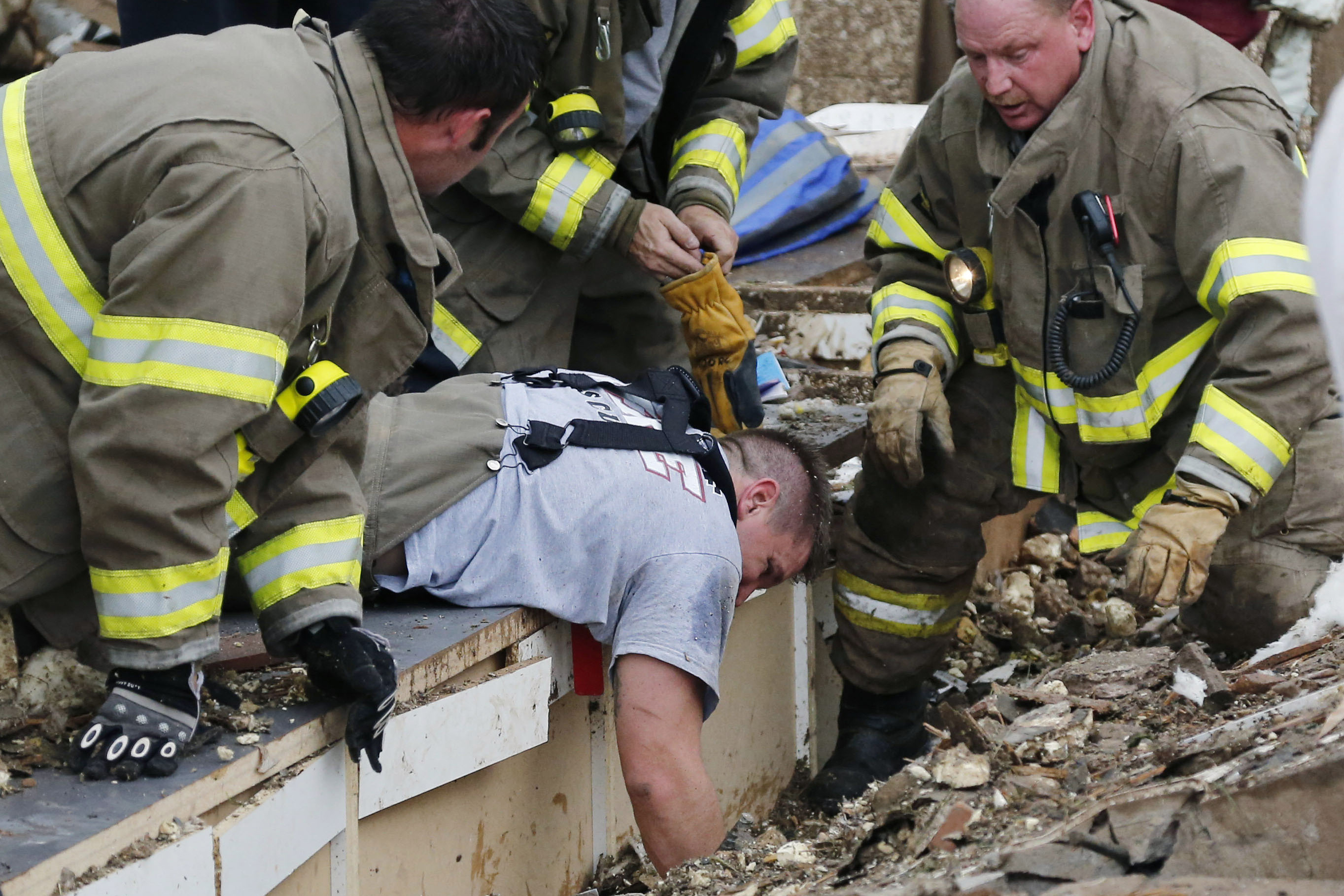 Rescue workers dig through the rubble of a collapsed wall at Plaza Tower Elementary School to free trapped students.