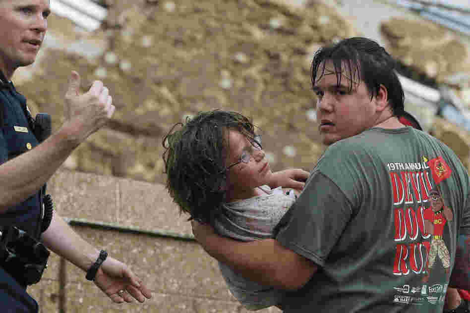 A child is carried from the rubble of Plaza Towers Elementary School.
