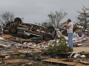 John Warner surveys the damage near a friend's mobile home in the Steelman Estates Mobile Home Park, destroyed in Sunday's tornado, near Shawnee, Okla., on Monday.