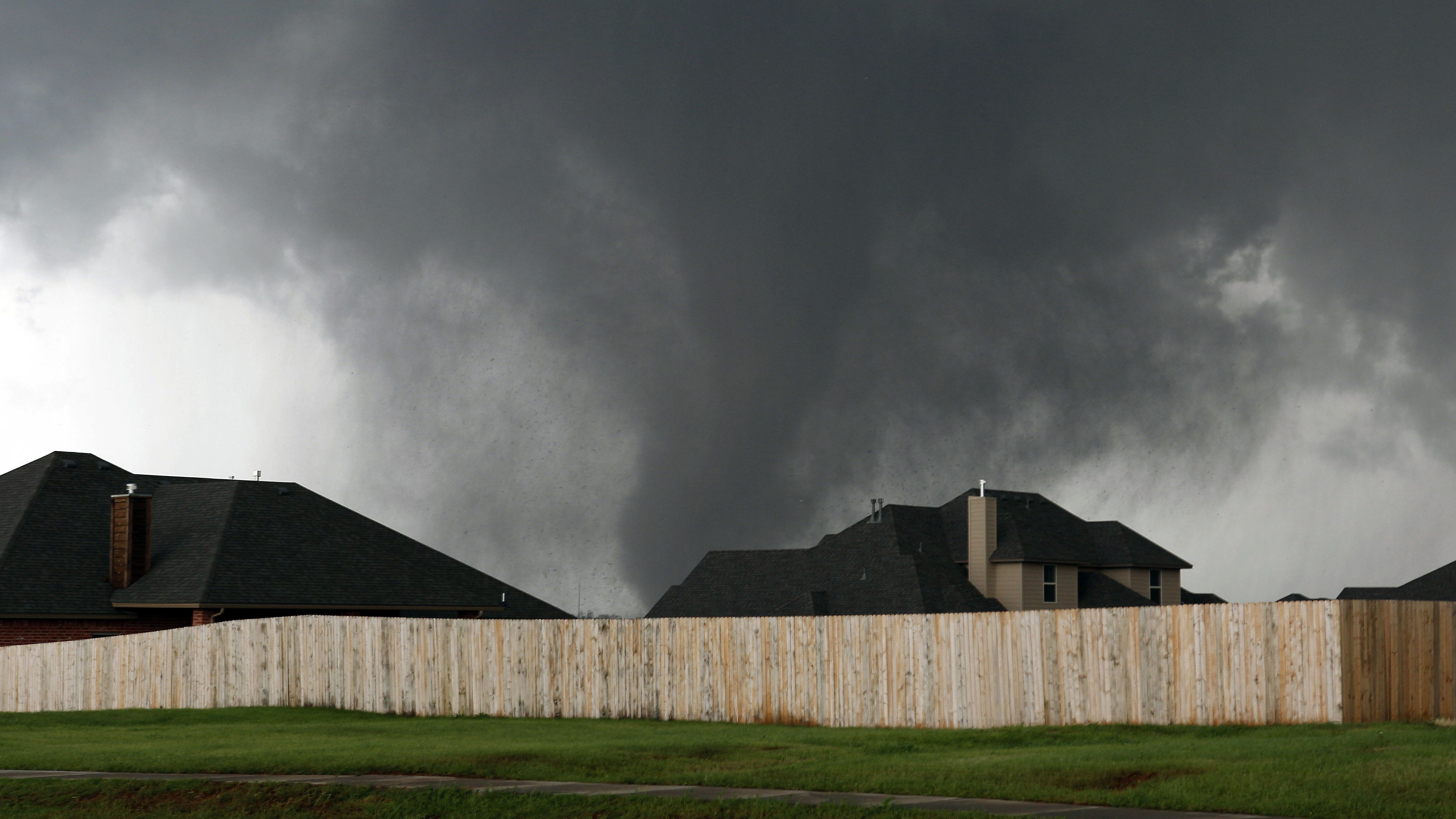 A tornado moves past homes in Moore on Monday.