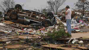 John Warner surveys the damage near a friend's mobile home in the Steelman Estates Mobile Home Park, destroyed in Sunday's tornado, near Shawnee, Okla., on Monday.