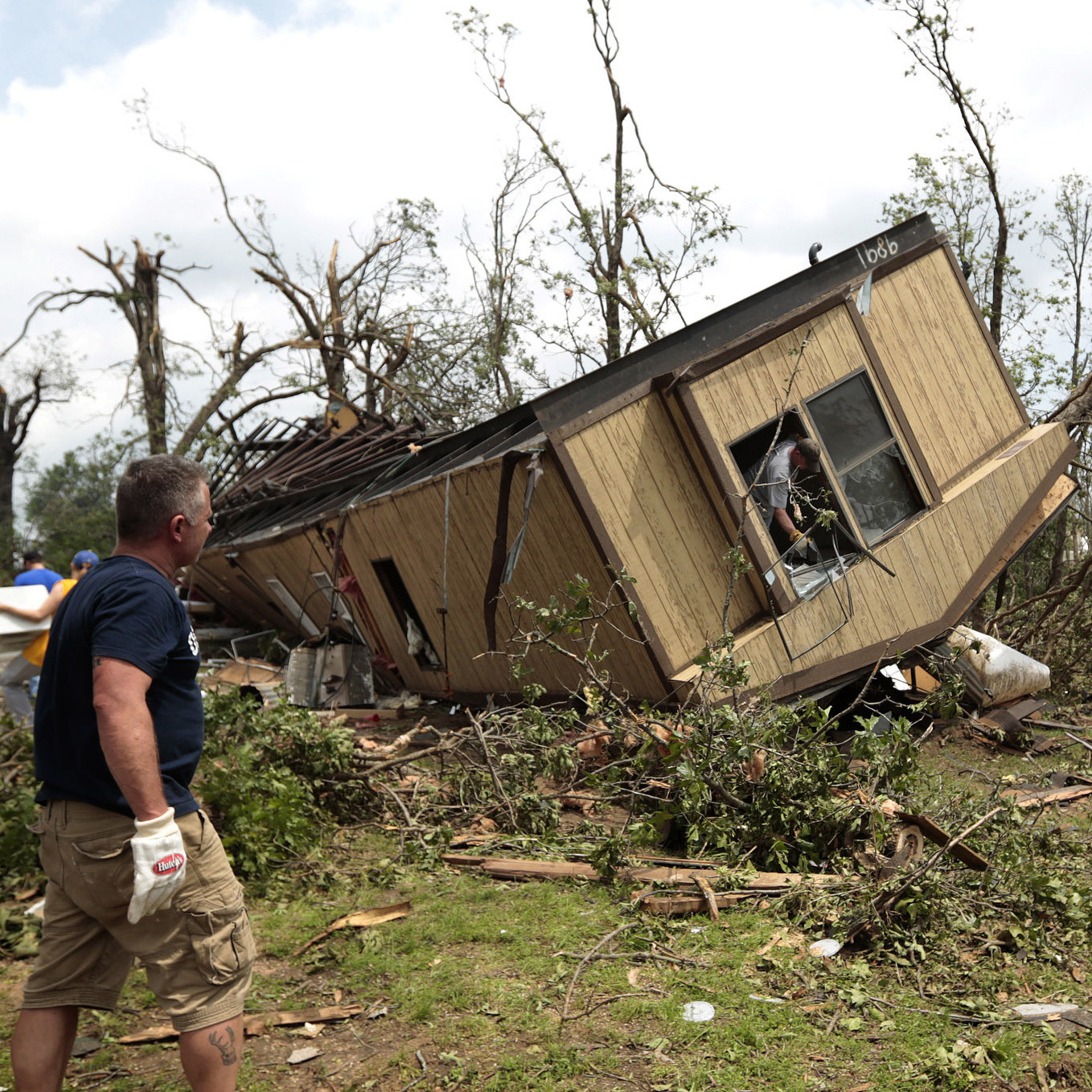 Volunteers help clean out Jean McAdams' mobile home after it was overturned by a tornado today near Shawnee, Oklahoma.
