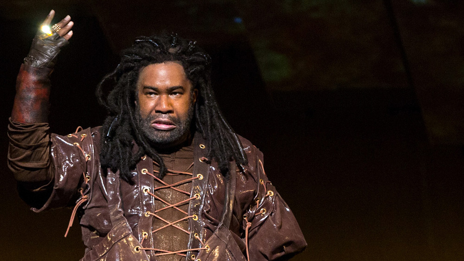 Eric Owens plays the greedy dwarf Alberich, displaying his golden ring, in Wagner's Das Rheingold. (Metropolitan Opera)