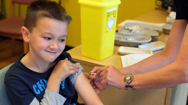 Luke Tanner, 7, gets vaccinated for measles at a clinic near Swanse