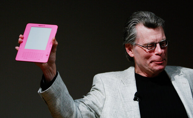 Stephen King holds a special pink Kindle given to him at a 2009 unveiling event for the Amazon Kindle 2.