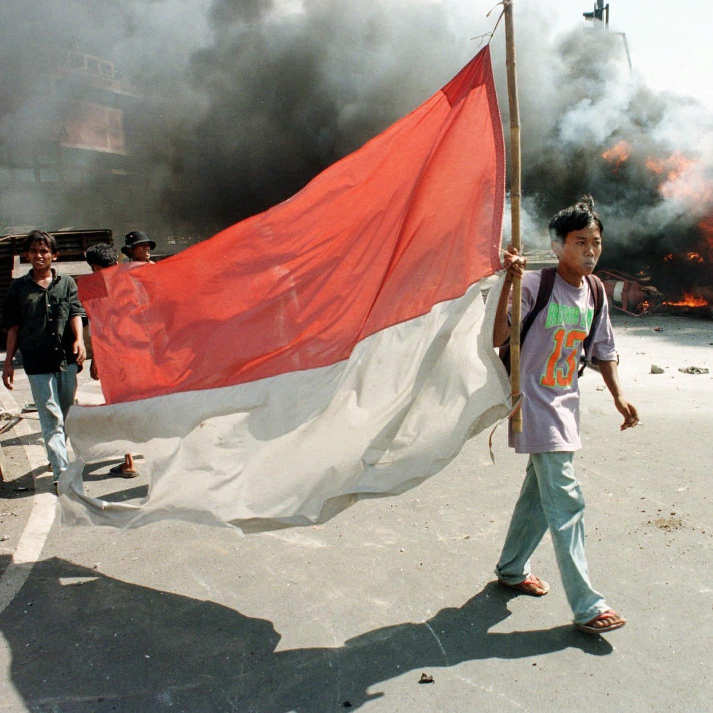 A protester carries an Indonesian flag during a street battle with police in front of Trisakti University in Jakarta on May 13, 1998.