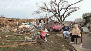 Barbara Garcia, right, sits with friends after a tornado destroyed much of their neighborhood in Moore, Okla. During an interview with CBS, Garcia found her dog buried in the wreckage of her house.