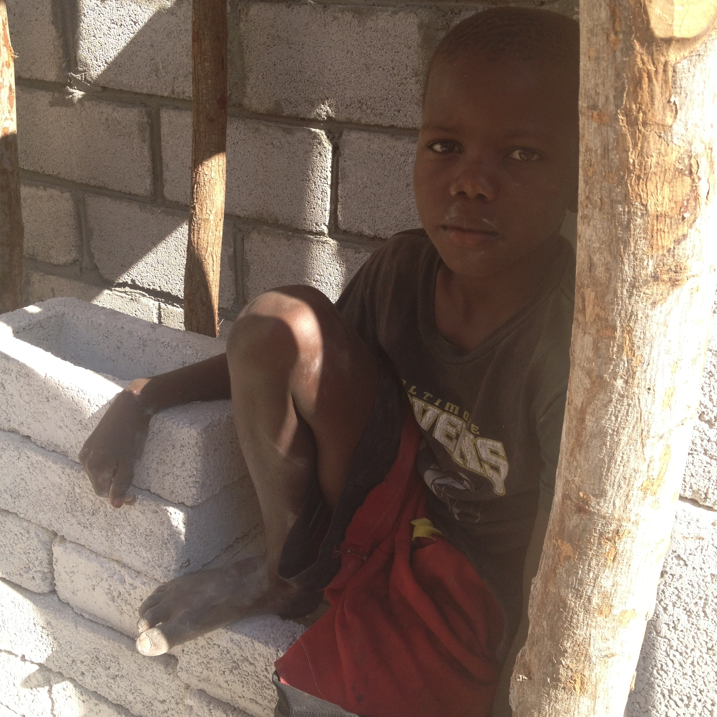 Edmon watches Tim's crew build his new school.