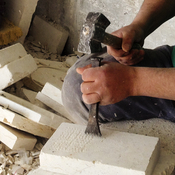 A worker chips away at Jerusalem stone, likely destined for a building facade somewhere in the world. Stone and marble is a big business in Palestinian towns near Bethlehem. Quarries are in Israeli-controlled areas and access can be a challenge.