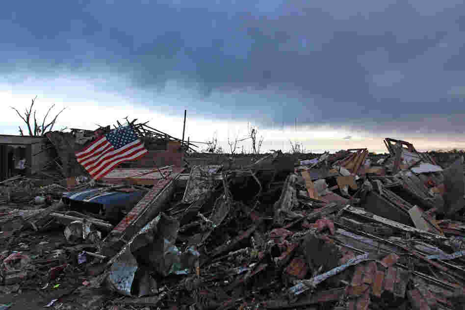 An American flag blows in the wind at sunrise atop the rubble of a home Tuesday, a day after a monstrous tornado moved through the Oklahoma City suburb of Moore, Okla.