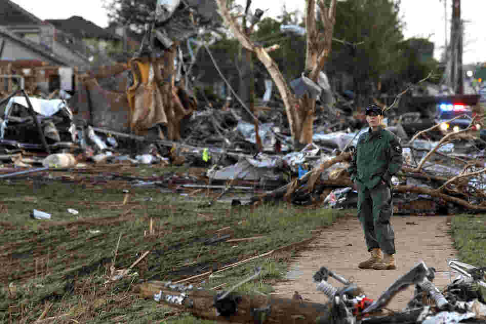 A security team member helps guard the rubble of a neighborhood in Moore, Okla.